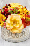 Bukett av orange rosor och höstväxter i keramisk vas för tappning Royaltyfria Bilder