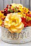 Bukett av orange rosor och höstväxter i keramisk vas för tappning Royaltyfri Foto