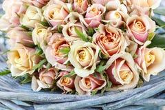 Bukett av pastellfärgade rosor i vide- korg för turkos arkivfoton