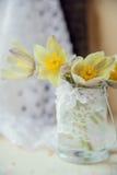 Bukett av primulor i rund vas med det pappers- hälsningkortet och kvinnors pärlemorfärg halsband Arkivfoto