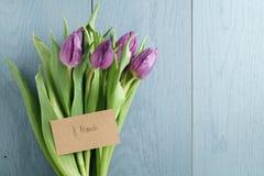 Bukett av purpurfärgade tulpan på den blåa wood tabellen med det pappers- kortet för 8 marsch Royaltyfria Bilder