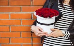 Bukett av röda rosor i en ask i händerna av flickan royaltyfri foto