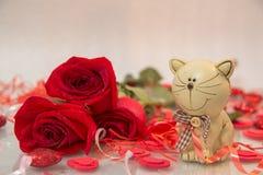 Bukett av röda rosor med en kattstatyett arkivbilder