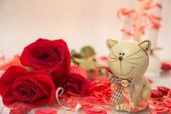 Bukett av röda rosor med en kattstatyett arkivfoton