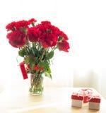 Bukett av röda rosor och det röda bandet med gåva på den wood tabellen Royaltyfri Bild