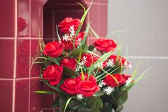 Bukett av röda rosor på graven arkivfoto