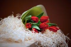 Bukett av röda tulpan på en tabell Arkivbild