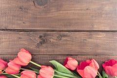 Bukett av röda tulpan på en träbakgrund med utrymme för text Royaltyfria Bilder