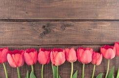 Bukett av röda tulpan på träbakgrund med utrymme för text Royaltyfri Foto