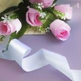 Bukett av rosor med bandet på ljus lila bakgrund royaltyfri bild