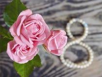 Bukett av rosor och den pärlemorfärg halsbandet i ett diagram 8 Kort för hälsning för dag för kvinna` s 8 mars Internationell lyc Royaltyfri Foto