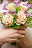 Bukett av rosor och freesior i händerna av bruden Arkivfoto