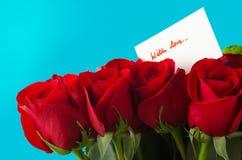 Bukett av rosor och kortet med förälskelse Arkivbild