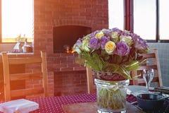 Bukett av rosor på en trätabell på verandan i ett landshus En familjberöm av årsdagen Royaltyfri Fotografi