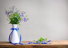 Bukett av små delikata blåa blommor av veronica i den vita vasen fotografering för bildbyråer