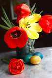 Bukett av tulpan för röd vår och handgjorda färgrika målade easter ägg mot lantlig träbakgrund Royaltyfri Foto
