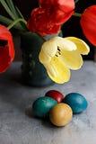 Bukett av tulpan för röd vår och handgjorda färgrika målade easter ägg mot lantlig träbakgrund Royaltyfri Bild