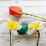 Bukett av tulpan för röd vår, påskliljor och handgjorda färgrika målade easter ägg mot lantlig träbakgrund Arkivbild