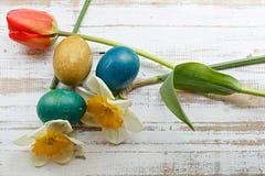 Bukett av tulpan för röd vår, påskliljor och handgjorda färgrika målade easter ägg mot lantlig träbakgrund Royaltyfria Bilder