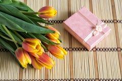 Bukett av tulpan och den rosa gåvaasken Arkivbild