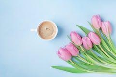 Bukett av tulpan och kaffekoppen på blå pastellfärgad bästa sikt för tabell Härlig vårfrukost på moder- eller kvinnas dag Lekmann royaltyfria bilder