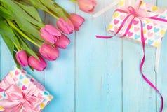 Bukett av tulpan på den blåa trätabellen med gåvaasken Lycklig dag för kvinna` s 8 mars , Dag för moder` s Lekmanna- lägenhet och Royaltyfri Fotografi