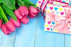 Bukett av tulpan på den blåa trätabellen med gåvaasken Lycklig dag för kvinna` s 8 mars , Dag för moder` s Lekmanna- lägenhet och Arkivbilder