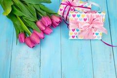 Bukett av tulpan på den blåa trätabellen med gåvaasken Lycklig dag för kvinna` s 8 mars , Dag för moder` s Lekmanna- lägenhet och Royaltyfri Foto