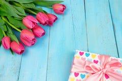 Bukett av tulpan på den blåa trätabellen med gåvaasken Lycklig dag för kvinna` s 8 mars , Dag för moder` s Lekmanna- lägenhet och Royaltyfri Bild