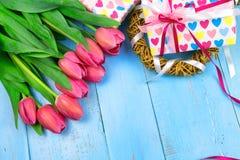 Bukett av tulpan på den blåa trätabellen med gåvaasken Lycklig dag för kvinna` s 8 mars , Dag för moder` s Lekmanna- lägenhet och Fotografering för Bildbyråer