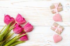 Bukett av tulpan, slågna in gåvor och stack hjärtor på en vit träbakgrund Arkivfoto