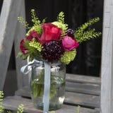 Bukett av vanliga hortensian, nejlikor och vanliga hortensior i en glass krus på trappan Arkivbild
