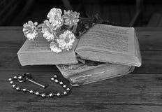 Bukett av vita blommor som ligger på två forntida böcker som ligger på en t royaltyfria foton
