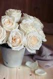 Bukett av vita rosor i en hink på en träbakgrund Arkivfoto
