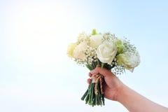 Bukett av vita rosor i hand på himlen Arkivbilder