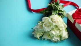 Bukett av vita rosor med den röda pilbågen på blå bakgrund Boxas gåva på sida