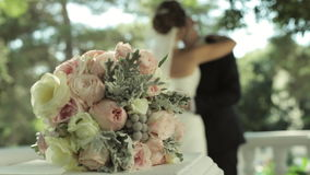 Bukett för brud` s och kyssande gift par på bakgrunden lager videofilmer
