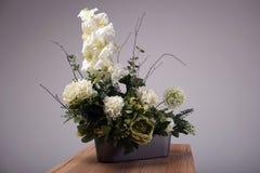 Bukett för konstgjorda blommor i vas på tabellen Arkivbild