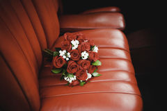 Bukett för röda rosor över den röda läderlagledaren Arkivfoto