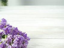 Bukett från purpurfärgade staticeblommor på en vit trätabell arkivfoto