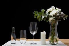 Bukett i vas med vattenflaskan och tomma exponeringsglas på tabellen bredvid stearinljuset Arkivbilder
