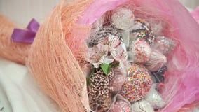 Bukett med liljor och sötsaker, godisar på tabellen nära kakan Panarama arkivfilmer