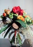 Bukett med olika blommor på den svarta tabellen i exponeringsglas Arkivfoton