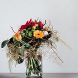 Bukett med olika blommor på den svarta tabellen i exponeringsglas Arkivbilder