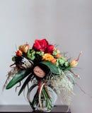 Bukett med olika blommor på den svarta tabellen i exponeringsglas Royaltyfri Bild