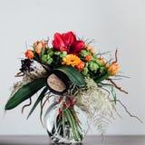 Bukett med olika blommor på den svarta tabellen i exponeringsglas Royaltyfria Bilder