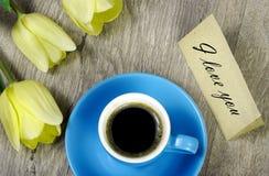 Bukett och en kopp kaffe tulpan för kaffekopp kaffe och en anmärkning älskar jag dig Inskriften älskar jag dig arkivfoton