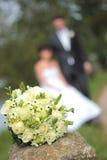 Bukett och nyligen gift par för bröllop Arkivfoto