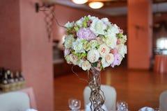 Buketten av blommor på ett ben i inre av restaurangen för en beröm shoppar floristry eller att gifta sig salongen fotografering för bildbyråer