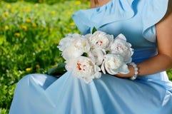 Buketten av den vita pionen blommar i flickans händer Arkivfoto